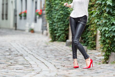 woman wearing red high heel shoes in city. woman wearing leather pants and red high heel shoes in city Stock Photography