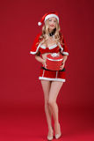 Sexy woman wearing santa claus clothes with Christmas gift. Sexy woman blond wearing santa claus clothes with Christmas gift on red background Stock Photography