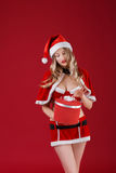 Sexy woman wearing santa claus clothes with Christmas gift Royalty Free Stock Photography