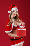 Sexy woman wearing santa claus clothes with Christmas gift. Portrait of happy sexy woman wearing santa claus clothes with Christmas gift on red background Stock Image