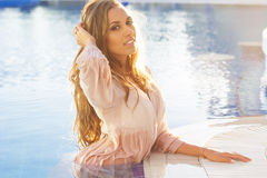 Sexy woman is wearing silk shirt in swimming pool Stock Photo