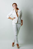Sexy woman wearing white suit. Beautiful sexy woman wearing white suit standing over white wall Stock Photos