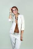 Sexy woman wearing white suit. Beautiful sexy woman wearing white suit standing over white wall Stock Image