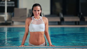 Sexy woman in white bikini show her sexy body in the swimming pool stock video