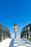 Sexy woman in white bikini standing on small bridge in sunny day Stock Photo