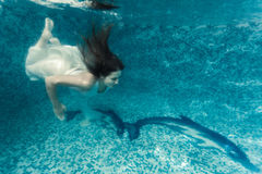 Sexy woman in white cloth diving underwater at pool Stock Photography