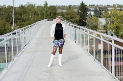 The sexy woman in a white jacket and white boots on the bridge Royalty Free Stock Image