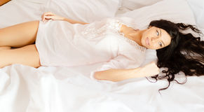 Sexy woman in white lace nightclothes lying on Royalty Free Stock Images