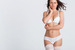 Sexy woman in a white lingerie on the background Stock Photography