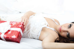 Sexy woman in white lingerie lying on a bed with red gift Royalty Free Stock Photos