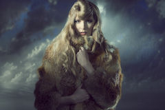 Woman with winter fashion style. Sensual blonde girl with long blonde hair and creative hair-style wearing warm fur coat on background and looking in camera Royalty Free Stock Images