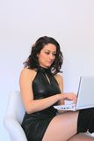 Sexy woman working on laptop. Sexy woman with a black mini dress working on a laptop while sitting on a white chair isolated on a white background Stock Photo