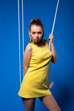 Sexy woman in yellow on swing with bright make-up Royalty Free Stock Images