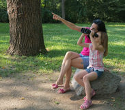 Sexy woman and young girl looking through binoculars. Mother and her daughter looking through binoculars in the park Stock Photography