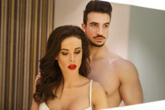 Sexy woman with young lover at mirror Stock Images