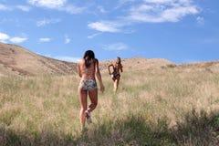 Sexy women in bikini running. On the open field Royalty Free Stock Photos