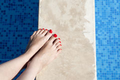 Sexy women legs splashing in swimming pool Royalty Free Stock Image