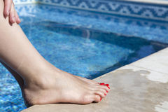 Sexy women legs splashing in swimming pool Royalty Free Stock Photos