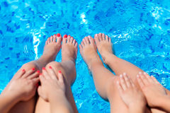 Sexy women legs splashing in swimming pool Stock Images