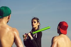 Woman holds baseball bat, men with muscular body. Women with makeup and fashionable hair in black holds green baseball bat, men in cap with muscular body and wet stock photo