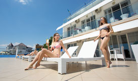 Sexy women are relaxing at a luxury hotel near a sea. Attractive young women in multi-colored bikinis are relaxing and. Two beautiful girls in bright swimsuits Royalty Free Stock Photography