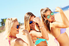 Sexy women showing muscles on the beach. A picture of a group of sexy women showing muscles on the beach Royalty Free Stock Image