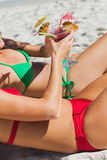 Sexy women taking sun clinking glasses of cocktail Stock Photos