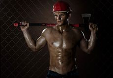 Workman. The beauty muscular worker chopper man, in safety helmet with big heavy ax in hands, tired appearance , on netting fence background stock photography