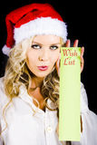 Sexy Xmas Woman Holding Christmas Wish List Sign. Attractive Young  Blonde Woman Wearing Santa's Hat Holding Christmas Wish List On Dark Studio Backdrop Stock Photos