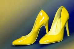 Yellow high heels shoes. The yellow high heels shoes are on blue and yellow background royalty free stock photography