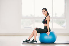 young Asian girl exercise, smile on fitness ball at clean home gym, sports club. Yoga aerobic class, sport trainer stock photos