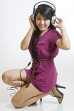 Sexy young Asian girl listening to music. Sexy young girl listening to music on headphones Stock Photos