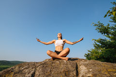 Sexy young athletic woman with muscular body practicing yoga on the rock. Blue sky background. Moment of harmony and Stock Photography