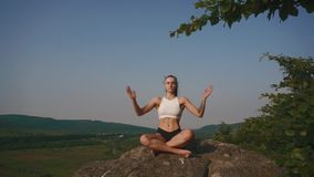 young athletic woman with muscular body practicing yoga on the rock. Blue sky background. Moment of harmony and stock video footage