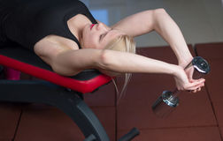 Sexy young athletics girl doing dumbbells press exercises. Fitness muscled woman in black sport clothing workout on bench in gym Royalty Free Stock Images