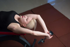 Sexy young athletics girl doing dumbbells press exercises. Fitness muscled woman in black sport clothing workout on bench in gym Stock Photo