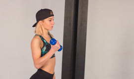 Sexy young athletics girl doing dumbbells press exercises. Fitness muscled woman in black sport clothing workout on bench in gym Royalty Free Stock Photos