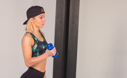 Sexy young athletics girl doing dumbbells press exercises. Fitness muscled woman in black sport clothing workout on bench in gym Royalty Free Stock Photo