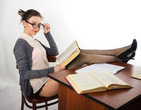 Sexy young beautiful female teacher sitting at a Stock Image