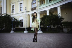 Sexy young beautiful girl in a gold dress stands on the square Royalty Free Stock Images