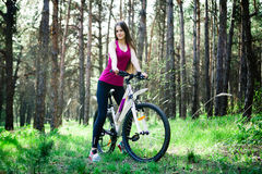 Sexy young beautiful sports girl on a white bicycle in the woods Royalty Free Stock Images