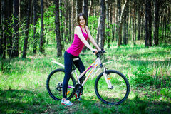 Sexy young beautiful sports girl on a white bicycle in the woods Stock Image