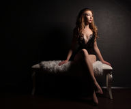 Sexy young beautiful woman in sensual black lingerie, sitting on white bench with fur, barefoot. Sexy young beautiful woman in sensual black lingerie, sitting Stock Images