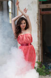 Sexy young beauty woman red dress in smoke Royalty Free Stock Photos