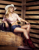 Sexy young blond cowgirl with fit body smiling on farm Stock Photos