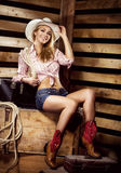 Sexy young blond cowgirl with fit body smiling on farm Royalty Free Stock Images