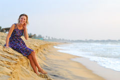 Sexy young blond girl sitting on beach. Sexy young blond girl sitting in dress on paradise beach Stock Photos