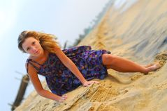 Sexy young blond girl sitting on beach Stock Image