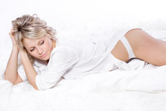 Sexy young blond woman in bedroom Stock Image