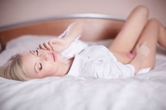 Sexy young blond woman laying in bed Stock Images